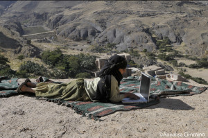 Yemen, kid surfing in internet on top of a mountain of the BaytBaws Village